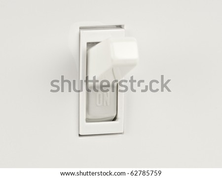 Traditional North American toggle electric light switch in ON position macro shot - stock photo