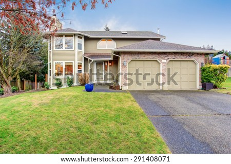 Traditional northwest house with driveway and garage. - stock photo