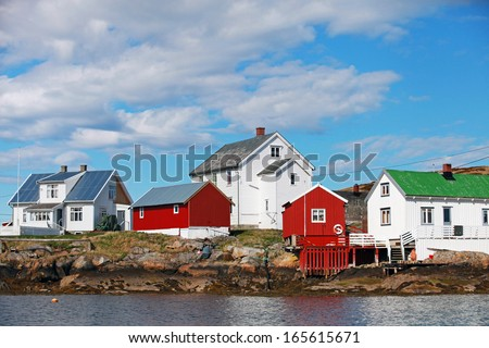 Traditional Norwegian coastal fishing village with red and white wooden houses - stock photo