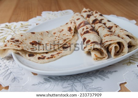 Traditional Norwegian holiday lefse rolled on a plate - stock photo