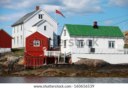 Traditional Norwegian village with red and white wooden houses on rocky sea coast - stock photo