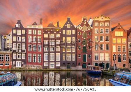 Traditional old buildings and boats at sunset in Amsterdam, Neth
