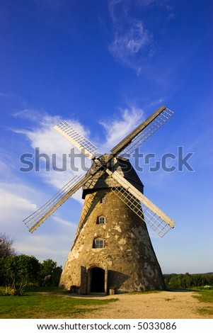 Traditional Old dutch windmill in Latvia against blue sky with white clouds
