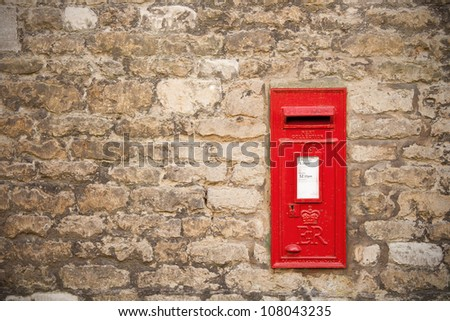 traditional old English red postbox mounted in a cotswold stone wall - stock photo