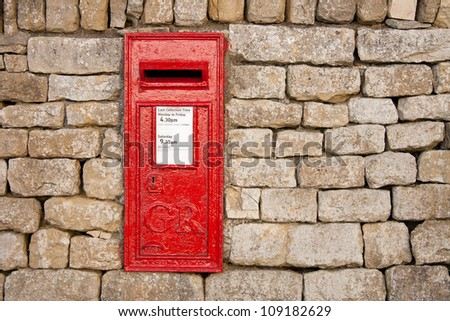 traditional old fashioned English red postbox mounted in a cotswold stone wall - stock photo