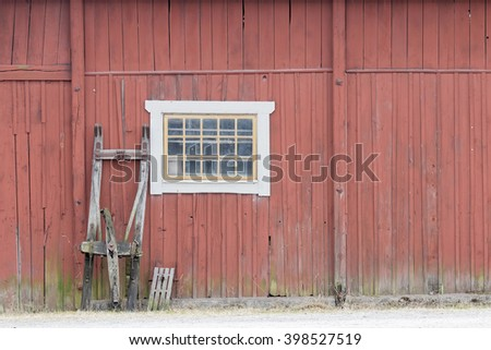 Traditional old red barn wall, a window and a sled - stock photo