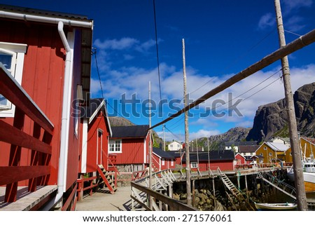 Traditional old red fishing huts in picturesque village of Nusfjord on Lofoten islands, Norway, popular tourist destination - stock photo