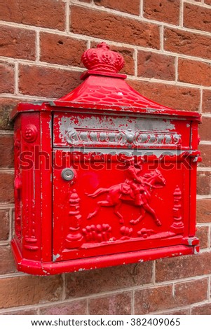 Traditional old red postbox mounted on a brick wall. - stock photo