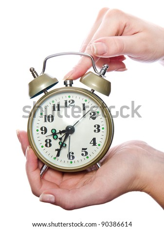 Traditional old-style alarm clock in woman's hands. isolated on white