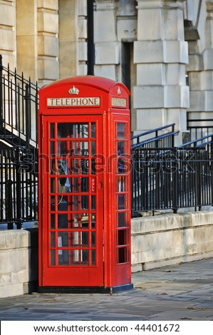 Traditional old style UK red phone box in warm early evening sun. - stock photo