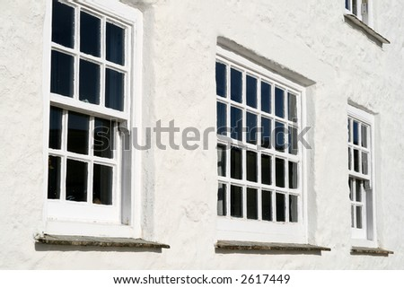 Traditional old windows and a white wall close up.