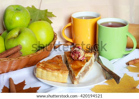 Traditional organic Apple Pie dessert, yeast dough, brown sugar, cinnamon, raisins, decorated with green apples, dried roses, colorful cups of tea and autumn foliage, close up view, selective focus - stock photo