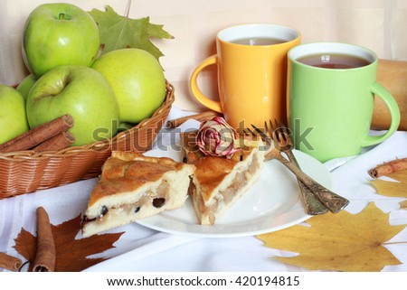 Traditional organic Apple Pie dessert, yeast dough, brown sugar, cinnamon, raisins, decorated with green apples, dried roses, colorful cups of tea and autumn foliage, close up view, selective focus