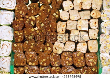 Traditional orient sweet - small pieces of turkish milk and chocolate delight (lokum) with pistachio and walnut on the shelve of confectioners shop in Istanbul, Turkey - stock photo