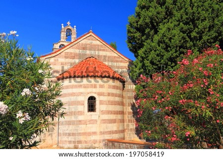 Traditional orthodox church surrounded by Mediterranean vegetation - stock photo