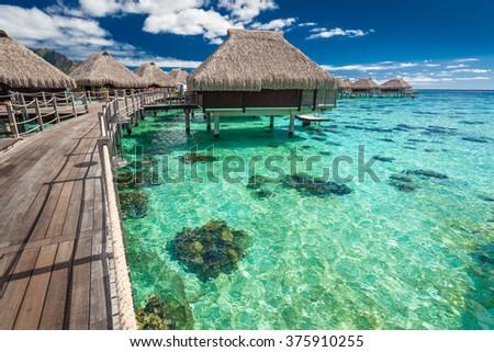 Traditional over water villas on a tropical lagoon of Moorea Island, Tahiti - stock photo
