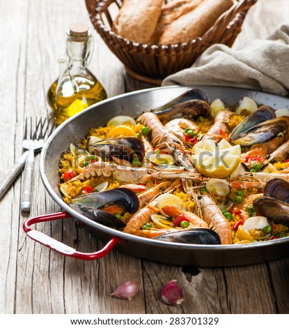 Traditional pan with spanish seafood paella on a rustic wooden table. Selective focus.