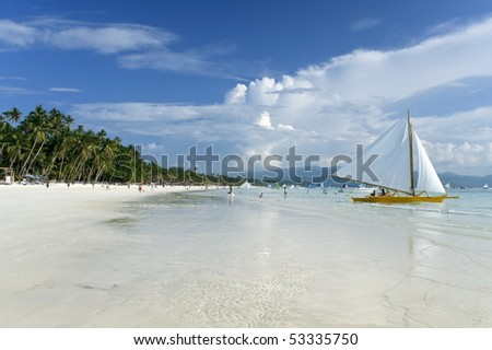traditional paraw sailing boats on white beach on boracay island in the philippines - stock photo