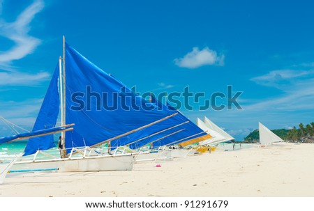traditional paraw sailing boats on white beach on boracay island, Philippines