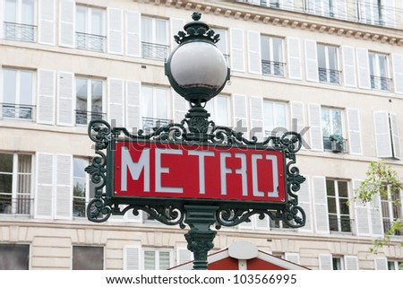 Traditional Paris metro sign against the backdrop of the building - stock photo