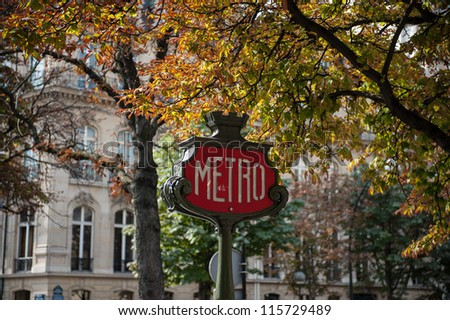 Traditional Paris metro sign with trees in the background - stock photo