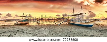 Traditional philippine boats bangka at sunset time - stock photo
