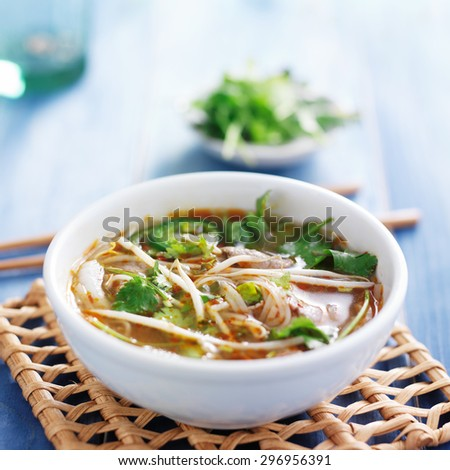 traditional pho tai beef vietnamese soup in bowl with cilantro and bean sprouts - stock photo