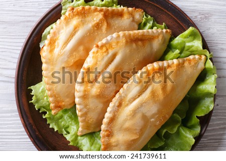 Traditional pies stuffed empanadas on a plate close-up. horizontal view from above  - stock photo