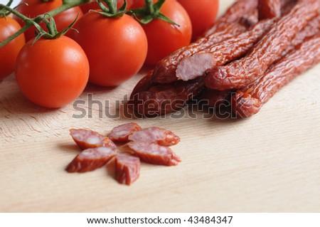 Traditional Polish Kabanosy sausages and tomatoes - stock photo