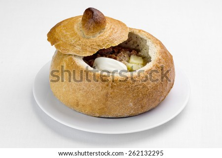 Traditional Polish soup made from fermented rye flour with sausages, eggs, meat and vegetables served in bowl made of bread  - stock photo