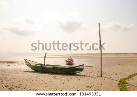 Traditional portuguese fishing boat on sandy beach in low tide, Aveiro - stock photo