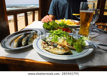 Traditional Portuguese lunch -  grilled sardines and chicken - at restaurant terrace with ocean beach view. Algarve, Portugal. - stock photo