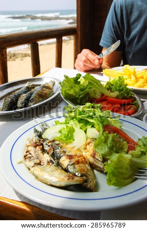 Traditional Portuguese lunch -  grilled sardines - at restaurant terrace with ocean beach view. Algarve, Portugal. - stock photo