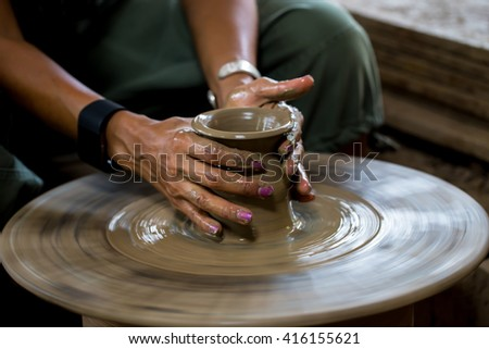 traditional pottery making, close up of potter's hands shaping a bowl on the spinning by clay, mold, crockery, earthenware, Thailand - stock photo