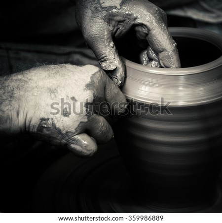 Traditional pottery master creates a clay jar on a potter's wheel. Potter hands closeup, black and white photo in retro style. Ancient craft and pottery handmade in vintage style. - stock photo