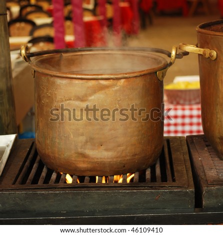 traditional preparation of  spanish meal in a copper ancient pan with burning fire at fair in barcelona - stock photo