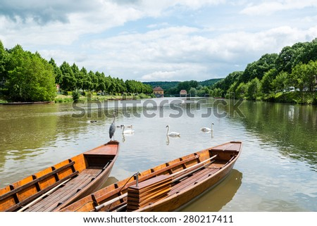 Traditional punt boats are waiting for tourists as passengers at the waterfront of Tubingen (Tuebingen) in the south of Germany. The traditional Stocherkahn (punt) is a typical sight of this city - stock photo