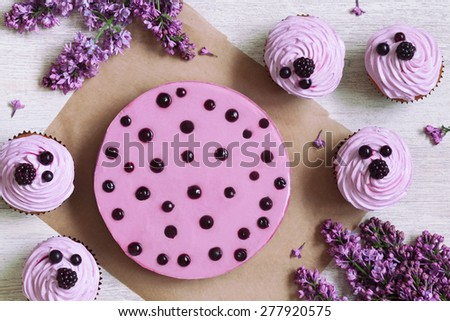 Traditional purple berry cupcakes with souffle dessert decorated with fresh berries on white kitchen table background. Rustic style and natural light. Top view. - stock photo