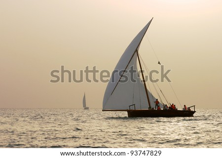 Traditional racing dhows dhows at sunset in the Arabian Gulf off Dubai. - stock photo