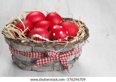 Traditional red and dotted Easter eggs in gray basket on rustic wood background.