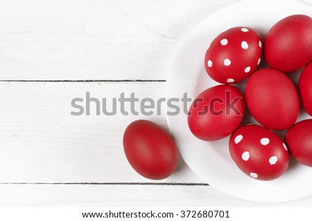 Traditional red and dotted Easter eggs in white plate on white wood background. Top view point.