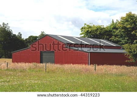traditional red barn in a field - stock photo