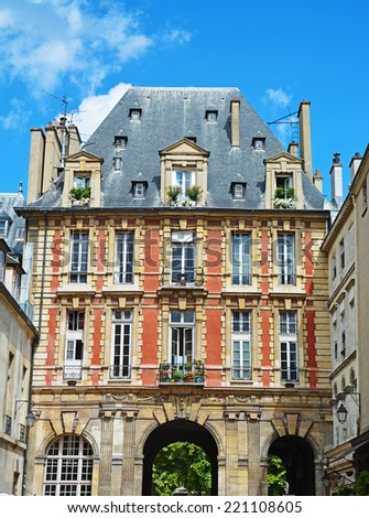 Traditional red facade in the Place des Vosges, Paris. France - stock photo