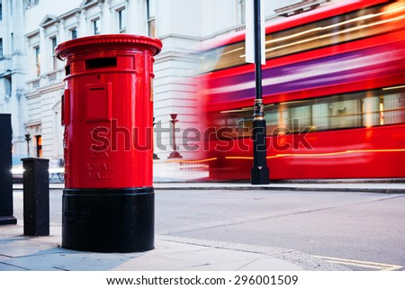 Traditional red mail letter box and red bus in motion in London, the UK. Symbols of the city and England - stock photo