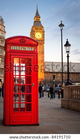 Traditional red phone booth in London with the Big Ben in the background near sunset - stock photo