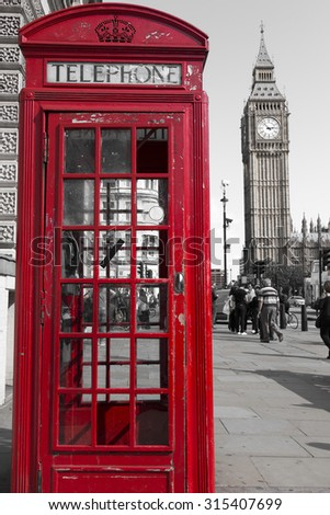 traditional red phone booths in London with the Big Ben in a desaturated background - stock photo