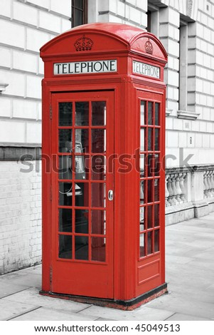 Traditional red telephone booth in London with a desaturated background - stock photo