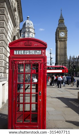 Traditional red telephone box in London public phone - a symbol of the city. Fragment of booths with the Big Ben in the background  - stock photo