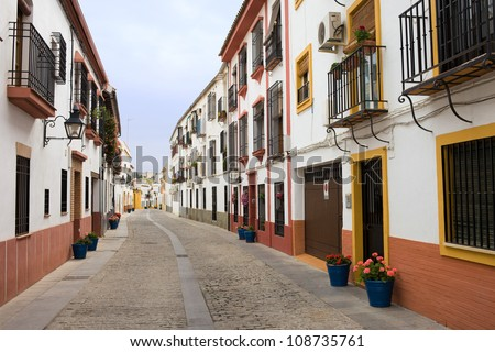Traditional residential architecture on a tranquil scenic street in the Old Town of Cordoba in Andalusia, Spain. - stock photo