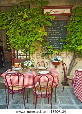 Traditional restaurant exterior with tables, chairs and menu, France - stock photo
